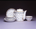 Pieces from a tea service with Chantilly sprig pattern: cup with handle, cup without handle (tea bowl), two saucers, and a teapot
